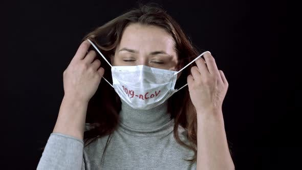 Thumbnail for Cute Girl Takes Off Facial Mask, Breathes, Looks at Camera. Global Pandemic Fear