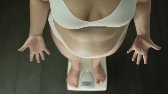 Thumbnail for Obese Woman Standing on Scales Desperately Gesturing Hands, Fat Belly, Top View