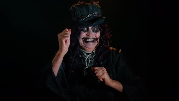 Frightening Senior Woman with Halloween Witch Makeup Listening Music Smiling Dancing to Disco Music