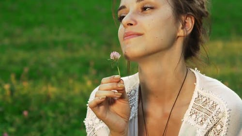 Girl Is Sniffing a Flower