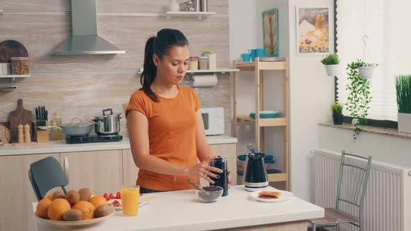 Fröhliche Frau Mahlen Kaffeebohnen