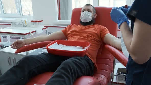 Thumbnail for A Donor with a Beard Lies on a Couch with a Red Rubber Heart on His Chest. Man Donates Venous Blood