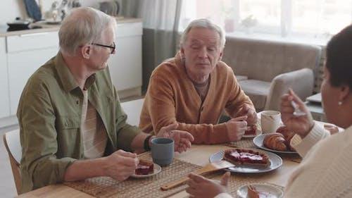 Older Men Having Cake and Tea