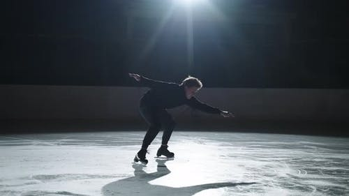 Professional Male Figure Skater Performs a Complex Figure Skating Element Flawlessly