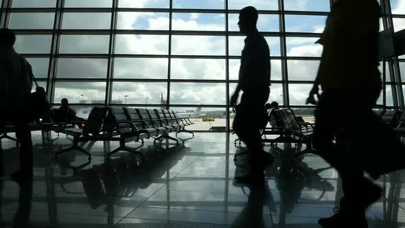 Thumbnail for Travelers Walking Along Window in Airport Terminal, People Silhouettes Walking.