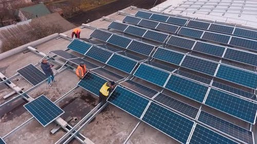 Workers install photovoltaic panels on roof