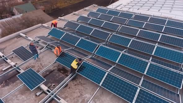 Thumbnail for Workers install photovoltaic panels on roof