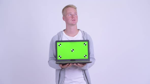 Thumbnail for Happy Young Blonde Handsome Man Thinking While Showing Laptop