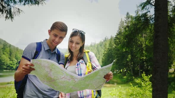 Adventures in the Mountains. Young Tourists Look at Their Location Map