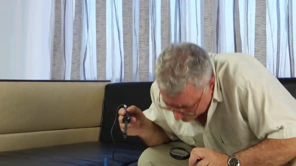 Thumbnail for Man Soldering a Board with a Soldering Iron, He Has in His Hands a Large Magnifying Glass
