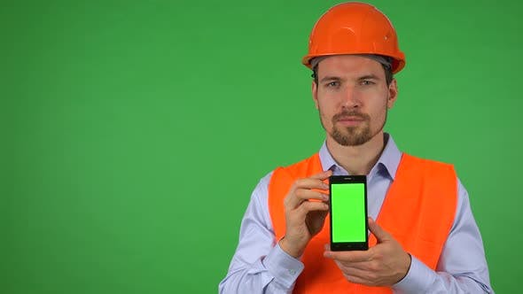 Thumbnail for A Young Construction Worker Shows a Smartphone with Green Screen To the Camera - Green Screen Studio
