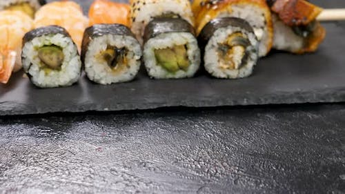 Traditional Japanese Sushi Rolls on a Black Plate