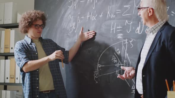 Thumbnail for Male Student Talking with Professor beside Chalkboard in High School