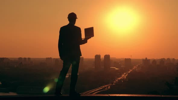 Businessman in a Hard Hat at Work Cityscape at Sunrise