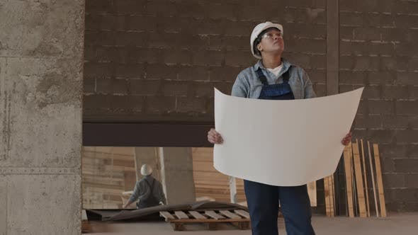 Construction Specialist Holding Large Paper