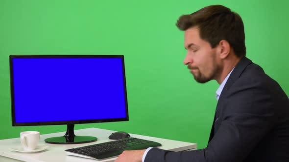 Thumbnail for A Young Businessman Sits in Front of a Computer and Shakes His Head at the Camera - Green Screen