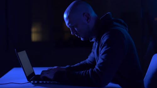 Hacker Using Laptop Computer for Cyber Attack