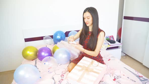 Beautiful Woman with Black Hair Sitting on Bed and Opens Birthday Presents