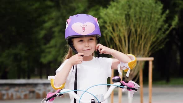 Thumbnail for Little Girl Put On The Protective Bicycle Helmet And Ride On Bike