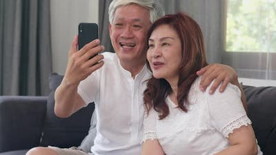 Asian senior couple video call using mobile phone video call talking with family.