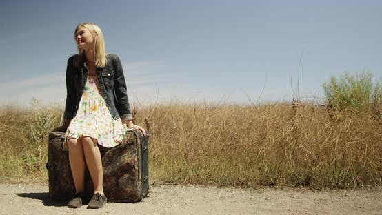 Thumbnail for Beautiful young woman sitting on a suitcase