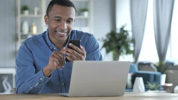 Cover Image for Young African Man Using Smartphone and Laptop at Work