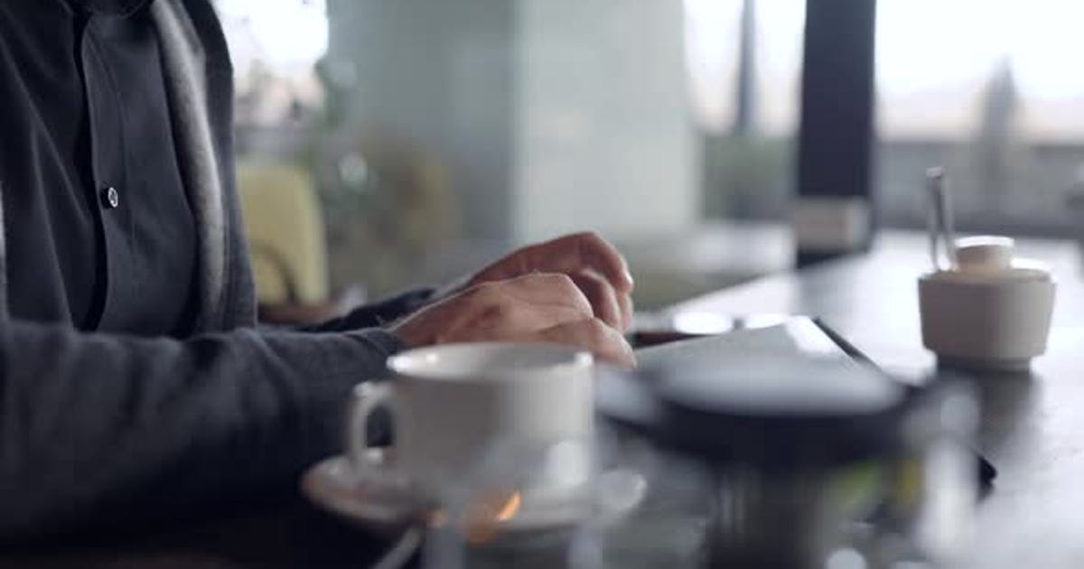 Close-up Shot of a Guy Chatting Online on a Tablet in Cafe, Cup of Tea on Table