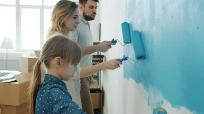 Young Couple with Child Remodelling House Painting Wall and Dancing Enjoying Music