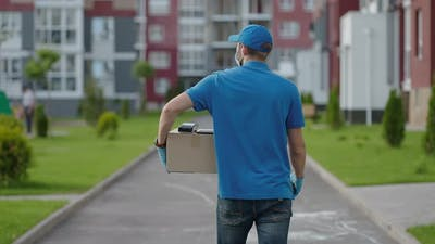 A Delivery Man Carries a Package to Customers in a Residential Area