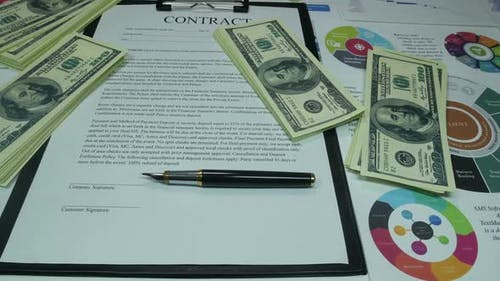 Financial Business Contract And Money On The Table In The Office Of The Company