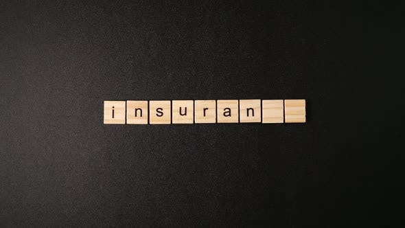"Cover Image for Wooden Cubes Open And Sets up A Word ""Insurance"""