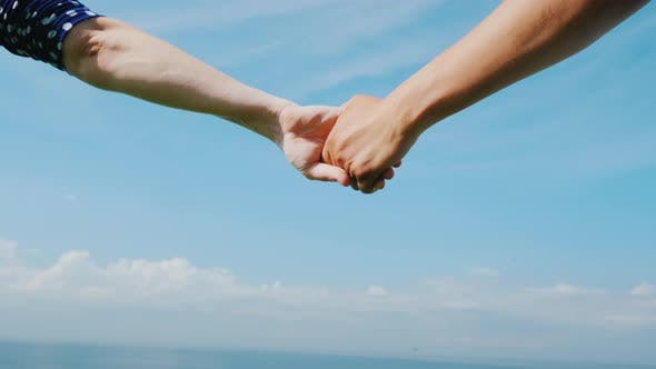 Cover Image for Young Couple Holds Hands Against a Blue Sky