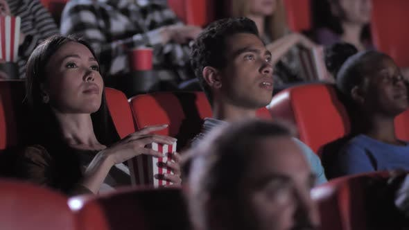 Mixed Race Couple Watching Scary Movie in Cinema
