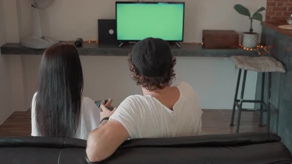 Cover Image for Man and Woman Sitting on Couch Playing Video Games on Green Screen