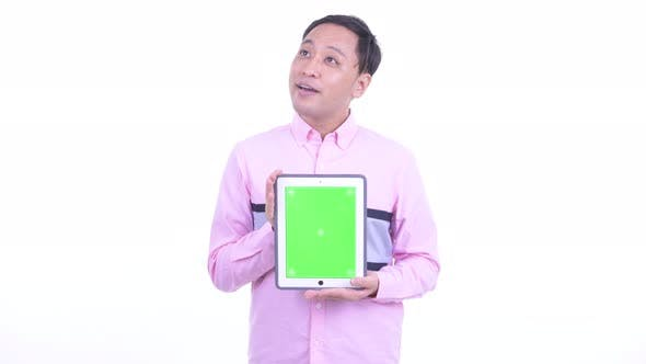 Thumbnail for Happy Japanese Businessman Thinking While Showing Digital Tablet
