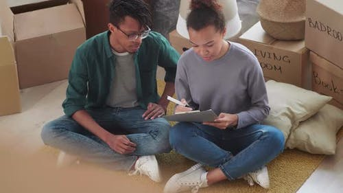 Young Couple Making List of Stuff