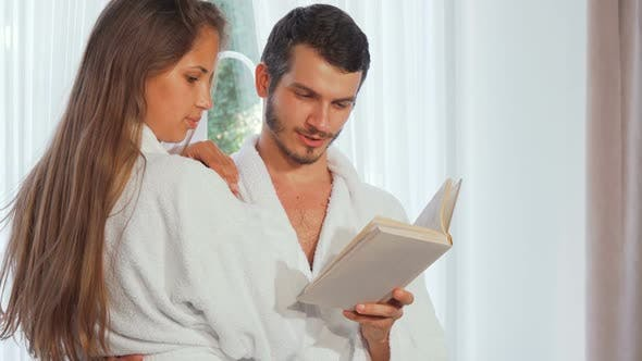 Thumbnail for Happy Couple Wearing Bathrobes Reading a Book Together 1080p