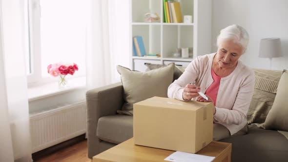 Thumbnail for Senior Woman Opening Parcel Box at Home