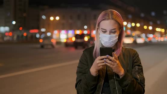 Woman Wearing Mask Looks in Smartphone Against Car Lights