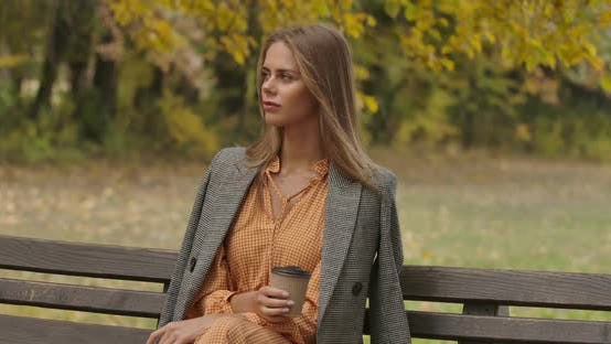 Cover Image for Beautiful Caucasian Woman Sitting on the Bench in the Autumn Park with a Cup of Coffee