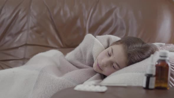 Thumbnail for Portrait Teenage Ill Girl Lying on the Sofa Covered with a Blanket at Home, She Is Cold. Nasal Spray
