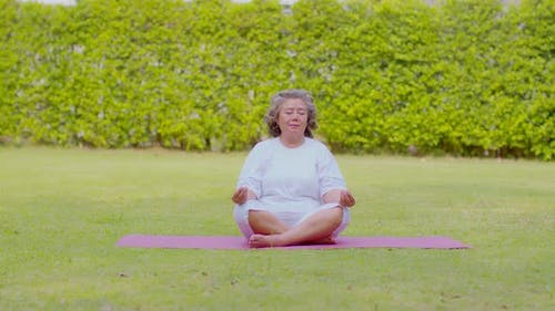 Calm of Healthy Asian Elderly woman with white hairs doing yoga lotus pose for meditation