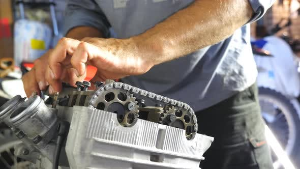 Thumbnail for View on Disassembled Motorcycle Engine. Hands of Professional Mechanic Repairing Motor. Repairer