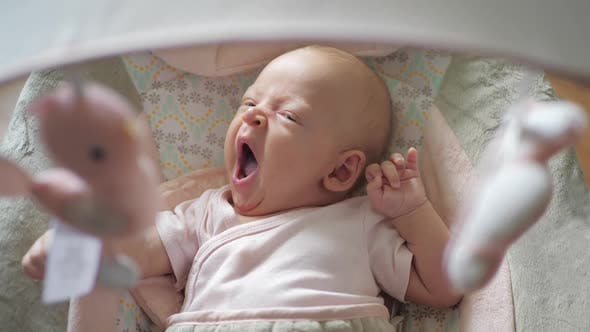Yawning Baby Girl in Child Rocker with Toys