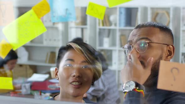 Thumbnail for Two Multiethnic Colleagues Discussing Post-It Memos