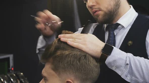 Cover Image for Cropepd Shot of a Professional Barber Cutting Hair of His Male Client