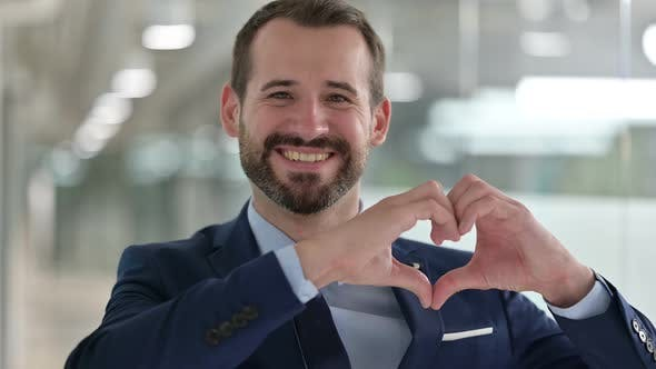 Portrait of Happy Businessman Showing Heart Sign with Hand