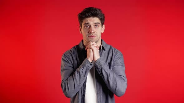 Thumbnail for Handsome Man in Shirt Praying Over Red Background. Guy Begging Someone.