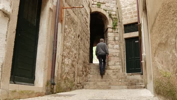 Tourist man walking through an alley in the streets of Dubrovnik