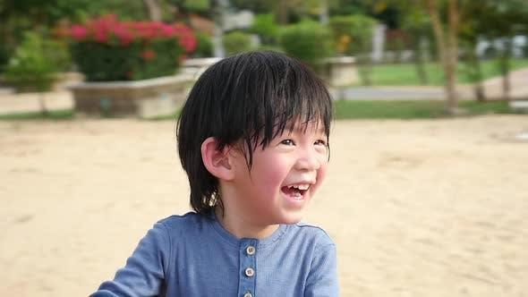 Asiatisches Kind hat Spaß auf dem Karussell im Freien